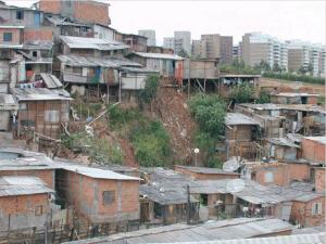 Resumen de la encíclica Laudato si. Foto de una favela. Al fondo se ven bloques de apartamentos.