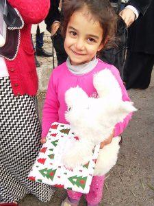 El drama de los refugiados. Foto de niña refugiada siria con regalos navideños