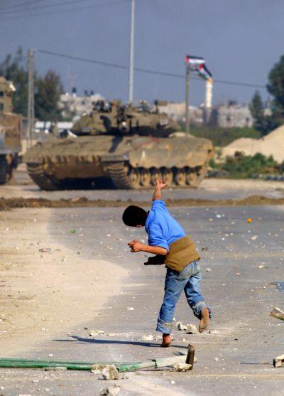 Niño palestino tirando piedras a un tanque israelí