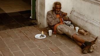 Fotografía de un pobre tumbado sobre el suelo