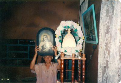 Doña Elvira en su casa levantando un cuadro que representa al Sagrado Corazón de Jesús