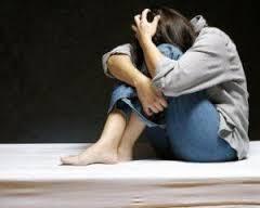Imagen de una chica joven sentada en el suelo y hecha un ovillo sobre sus piernas dobladas