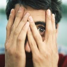 Fotografía de un chico que se tapa la cara con las manos y al que solamente se le ve el pelo y un ojo que aparece muy abierto entre dos de sus dedos.