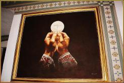 Cuadro que representa las manos de un sacerdote alzando la hostia después de la consagración