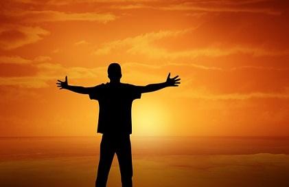 Jesús de Nazaret es buena noticia para los hombres de buena voluntad. Fotografía en la que aparece un hombre con los brazos extendidos mientras contempla la salida del sol