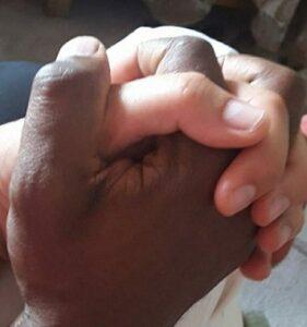 La oración en la enseñanza de Jesús de Nazaret. Manos entrelazadas. La mano derecha de un hombre negro con la mano izquierda de una mujer blanca.