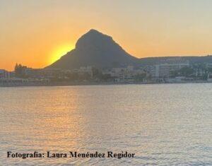 Brille así vuestra luz ante los hombres. Fotografía en la que aparece el sol poniéndose detrás de una montaña. El mar en primer plano. Fotografía de Laura Menéndez Regidor