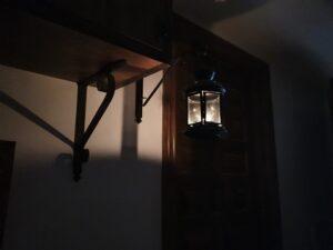 Brille así vuestra luz ante los hombres. Fotografía de un farol en una habitación a oscuras